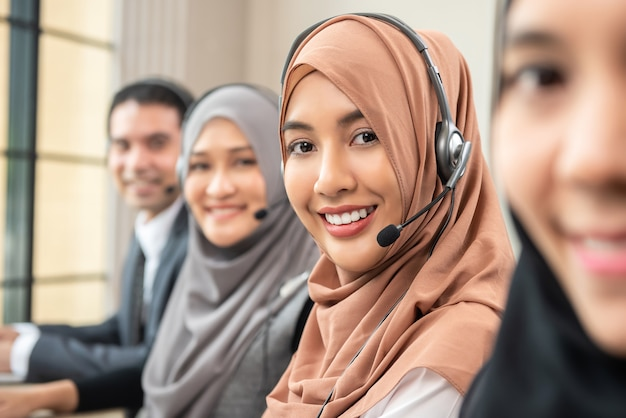 Smiling asian muslim women working  in call center with team Premium Photo