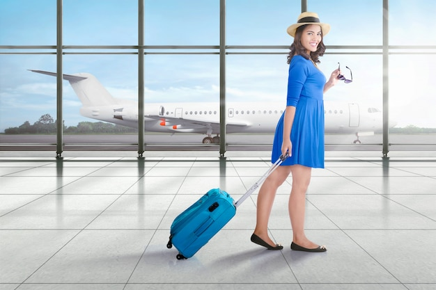 Smiling asian traveler woman with suitcase walking Premium Photo