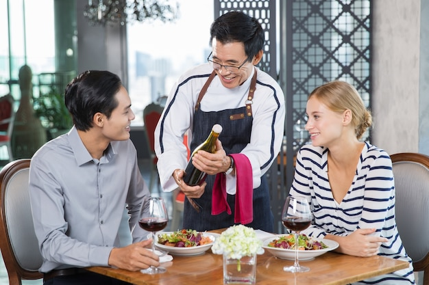 Smiling asian waiter offering wine to young couple Free Photo