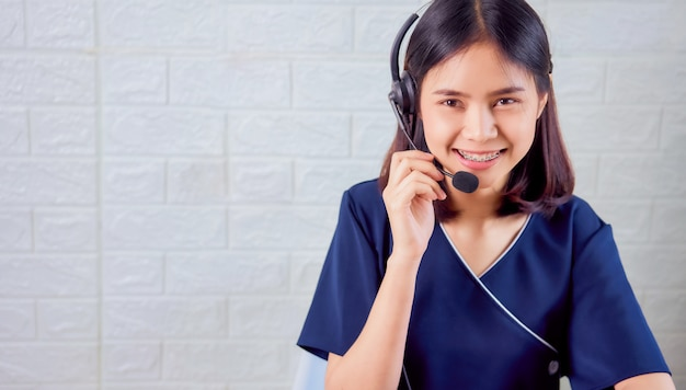 Smiling asian woman consultant wearing microphone headset of customer support phone operator at workplace. Premium Photo