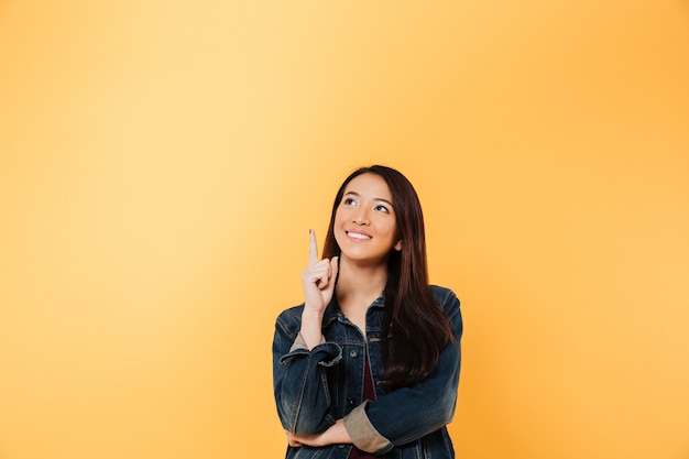 Smiling asian woman in denim jacket pointing and looking up over yellow background Free Photo