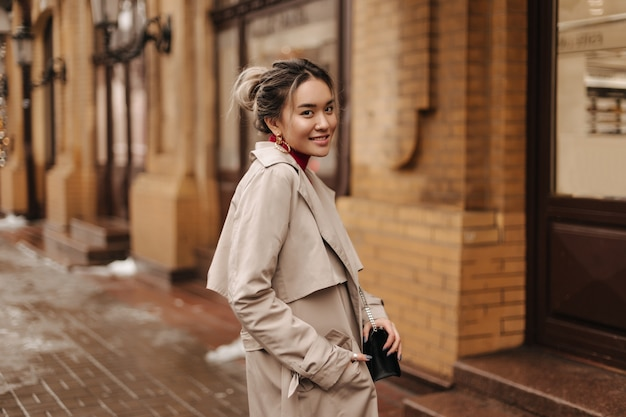 Smiling asian woman dressed in beige autumn coat holding crossbody bag and posing against brick old building Free Photo
