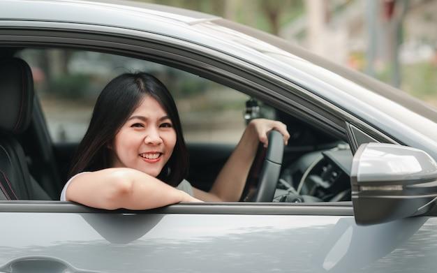 Ся азиатская женщина управляя ее новым автомобилем Premium Фотографии