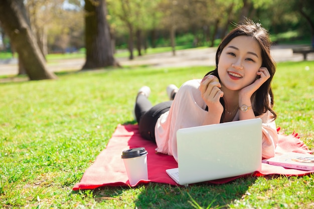 Smiling asian woman eating apple and using laptop on lawn Free Photo
