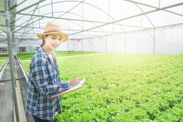 Smiling asian woman farmer hand hold document file in greenhouse green oak hydroponic organic nursery farm. Premium Photo