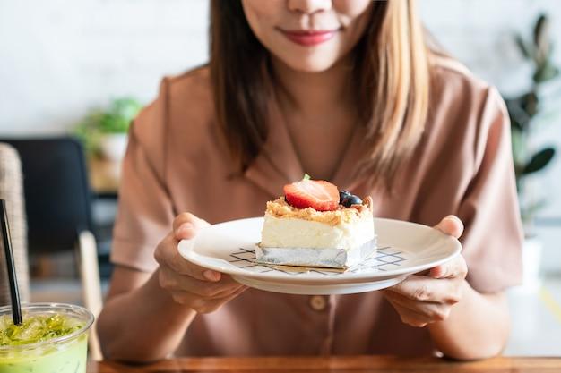 カフェの木製テーブルに彼女のお気に入りのイチゴのチーズケーキのプレートを保持している笑顔のアジアの女性。 Premium写真
