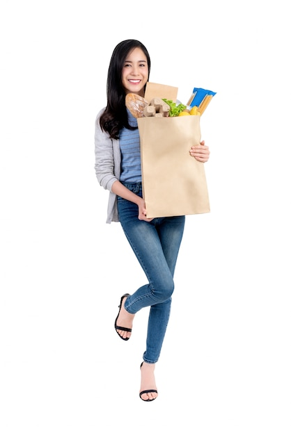 Smiling asian woman holding paper shopping bag full of vegetables and groceries Premium Photo