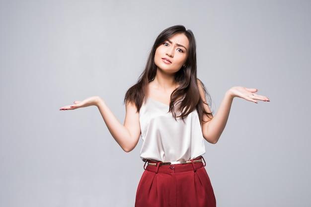 白い壁に分離された製品のコピースペースを示すアジアの女性の笑みを浮かべてください。 無料写真