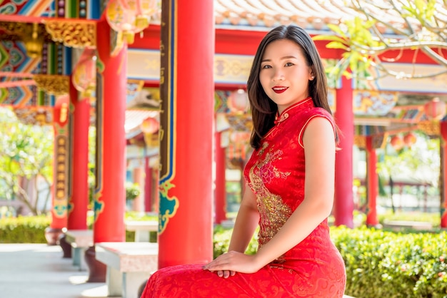 8e43eb096 Smiling asian woman in traditional red chinese cheongsam qipao dress ...