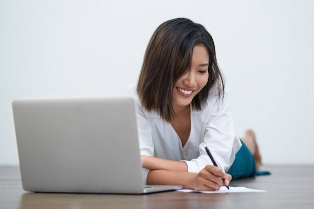 Smiling Asian Woman Writing on Floor with Laptop Free Photo