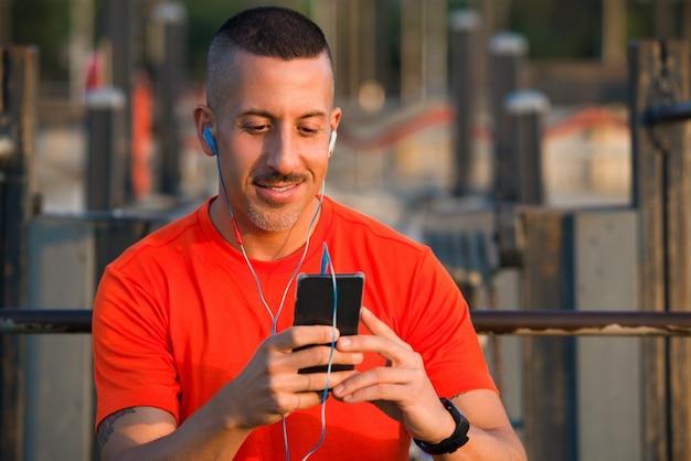 Atleta sorridente che scarica musica a smartphone Foto Gratuite