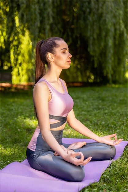 Smiling athletic woman is doing yoga Free Photo