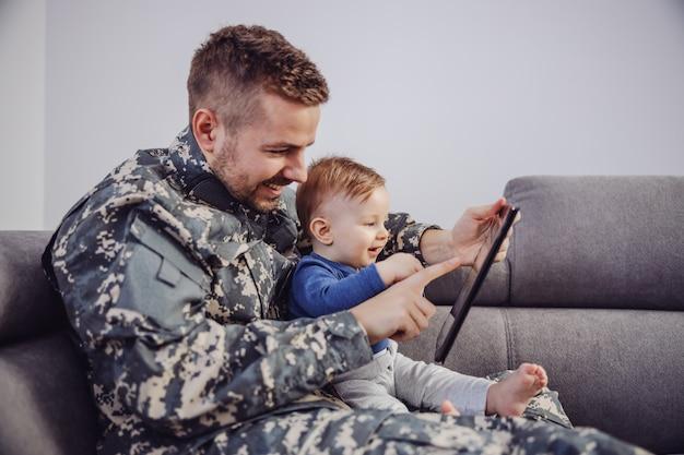魅力的なひげを生やした兵士が彼の幼い息子と一緒にリビングルームのソファーに座っていると、タブレットでゲームをプレイします。 Premium写真