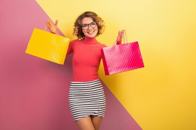 Улыбающаяся привлекательная возбужденная женщина в стильном красочном наряде с сумками на розово-желтом фоне, шопоголик в продаже, модная летняя тенденция Бесплатные Фотографии