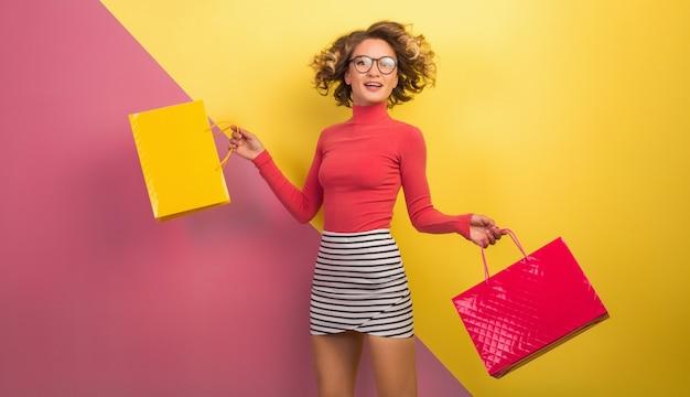 Улыбающаяся привлекательная возбужденная женщина в стильном красочном наряде с сумками для покупок Бесплатные Фотографии