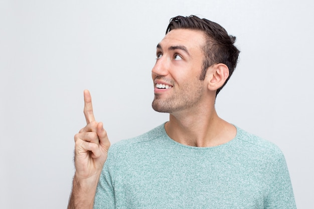 Smiling attractive man pointing upwards Free Photo