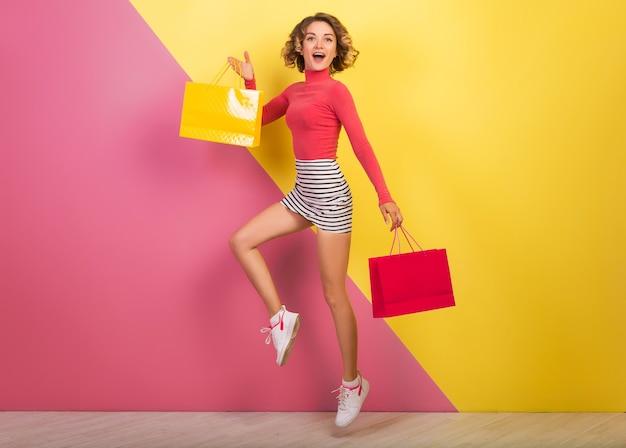 Улыбающаяся привлекательная женщина в стильной красочной одежде, прыгающая с сумками, счастливая, розово-желтый фон, шея поло, полосатая мини-юбка, распродажа, скидки, шопоголик, модный летний тренд, эмоциональный Бесплатные Фотографии