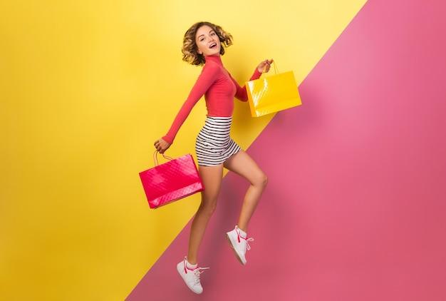 Donna attraente sorridente in vestito colorato elegante che salta con le borse della spesa su sfondo rosa giallo, collo a polo, minigonna a righe, shopaholic in vendita, tendenza estate moda Foto Gratuite
