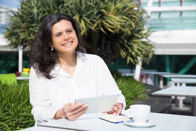 Smiling attractive woman working and using tablet in street cafe Free Photo