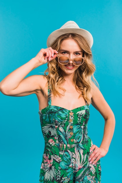 Smiling attractive young woman in flowered dress and hat holding sunglasses Free Photo