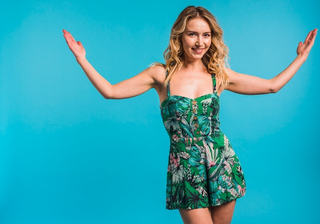 Smiling attractive young woman in flowered dress with hands to sides Free Photo