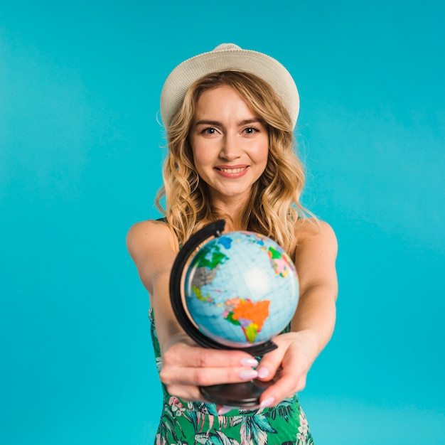 Smiling attractive young woman in hat and dress showing globe Free Photo