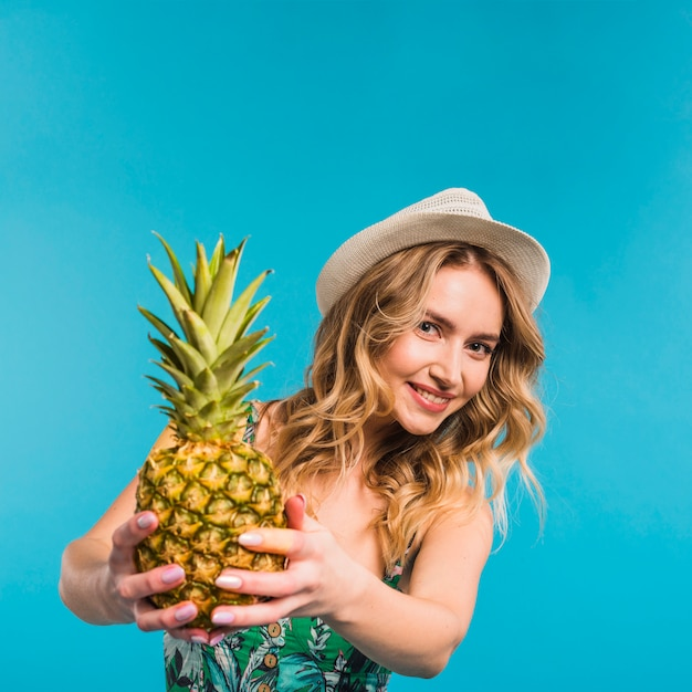 Smiling attractive young woman in hat holding fresh pineapple Free Photo