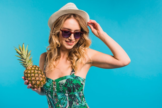 Smiling attractive young woman in hat and sunglasses holding pineapple Free Photo