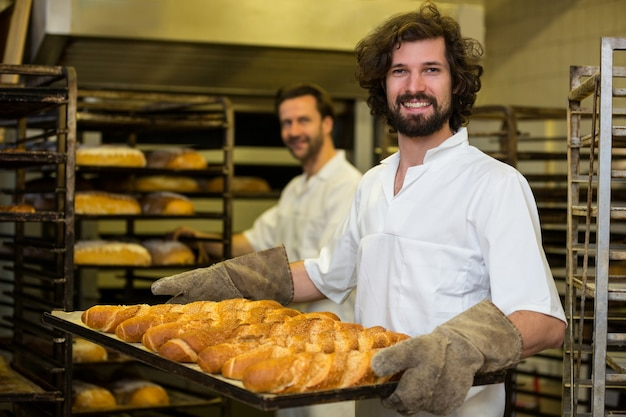 Smiling baker carrying a tray of freshly baked french baguette Free Photo