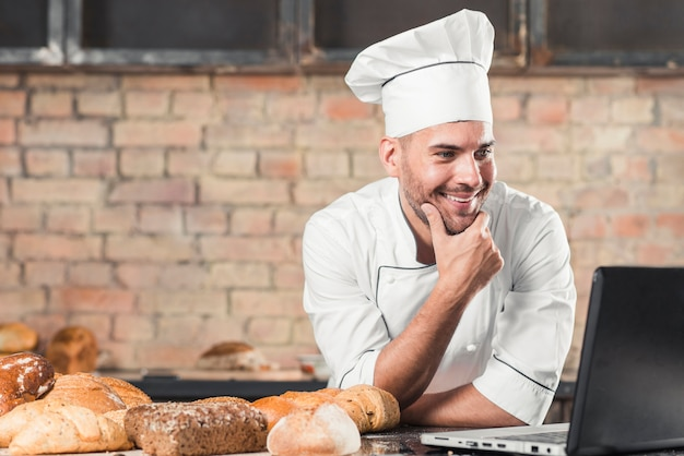 Smiling baker looking at laptop over the kitchen worktop with baked breads Free Photo