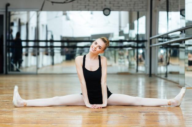 Улыбающаяся балерина делает шпагат в балетном классе Premium Фотографии