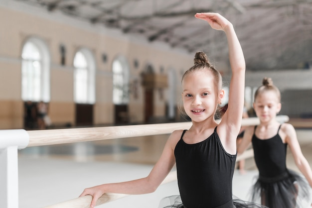 Smiling ballet dancer practicing with barre in dance class Free Photo