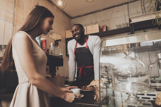 Smiling barista man gives a girl her order Premium Photo