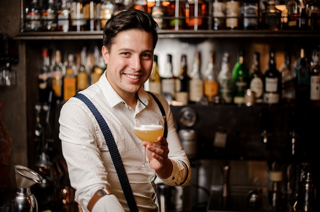 Smiling barman holding a coctail at the bar stand Premium Photo