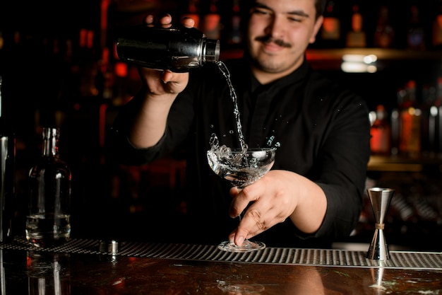 Smiling bartender pouring a transparent alcohol into the cocktail glass from the steel shaker Premium Photo
