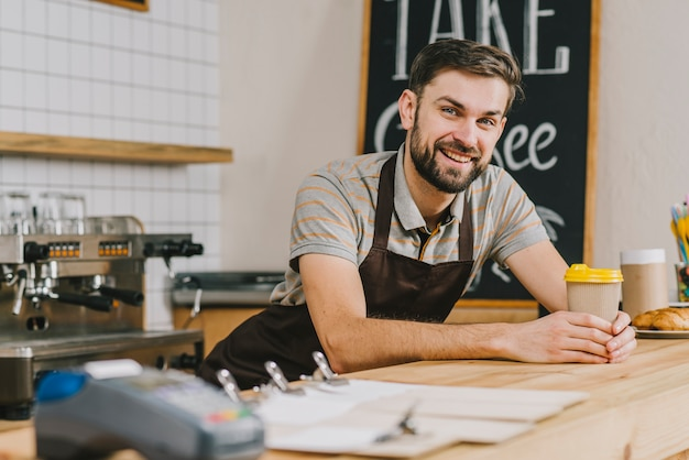 Smiling bartender with hot beverage Free Photo
