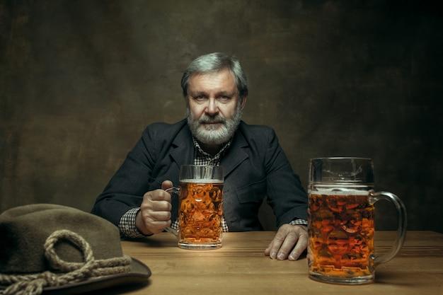 Улыбающийся бородатый мужчина пьет пиво в пабе Бесплатные Фотографии