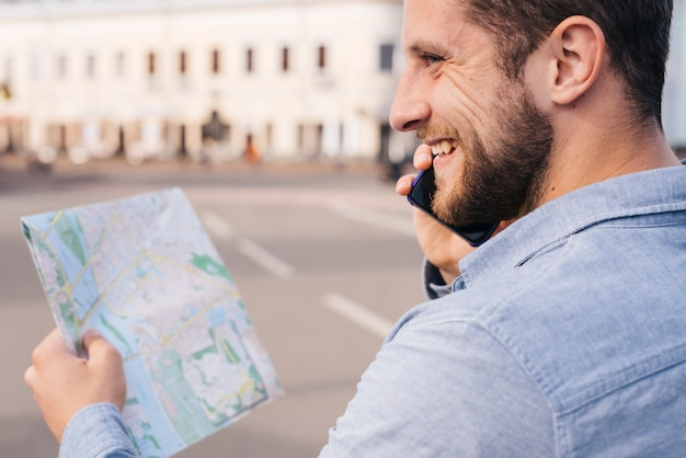 Smiling bearded man holding map while talking on cell phone Free Photo
