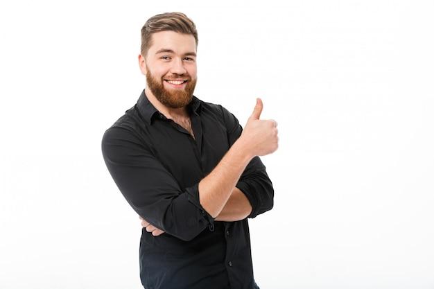 Uomo barbuto sorridente in camicia che mostra pollice in su Foto Gratuite