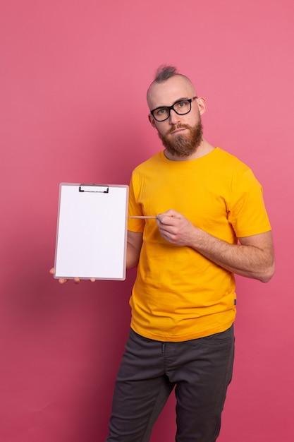 빈 종이 가리키는 클립 보드를 들고 캐주얼 옷을 입고 안경을 쓰고 수염 난된 남자 미소 무료 사진