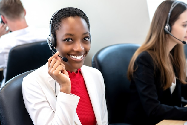 Smiling beautiful african american woman working in call center with diverse team Premium Photo