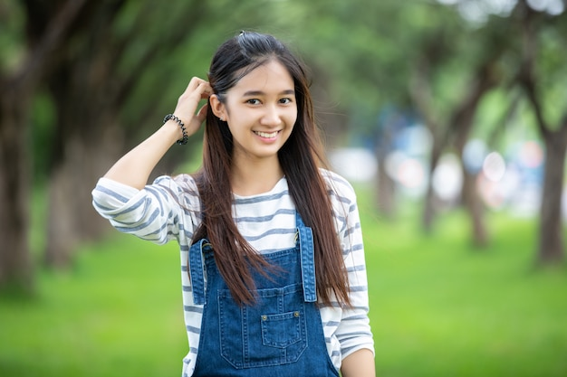 Smiling beautiful asian girl at tree on park in summer for relax time Premium Photo