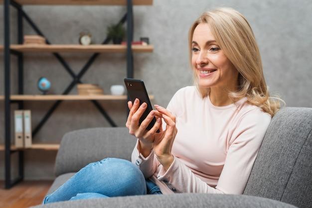 Smiling beautiful blonde young woman sitting on sofa using smart phone Free Photo