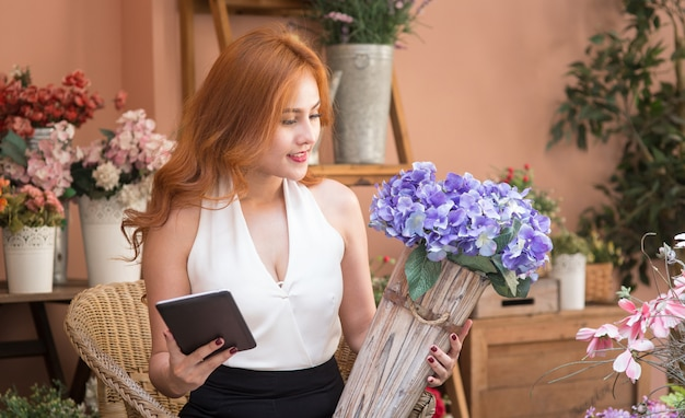 Smiling beautiful business woman check order in flower shop Premium Photo