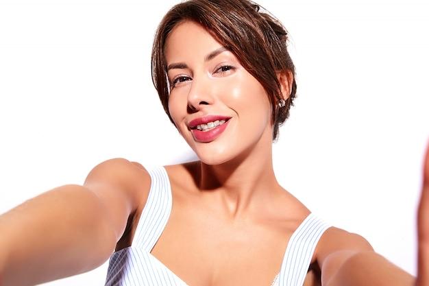 휴대 전화에서 셀카 사진을 만드는 치아에 흰색 교정기와 메이크업없이 캐주얼 여름 드레스에 아름 다운 귀여운 갈색 머리 여자 모델 미소, 절연 무료 사진