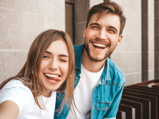 Smiling beautiful girl and her handsome boyfriend in casual summer clothes. happy family taking selfie self portrait of themselves on smartphone camera.having fun on the street. shows tongue Free Photo