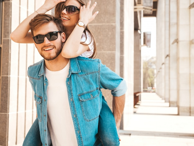 Smiling beautiful girl and her handsome boyfriend in casual summer clothes. man carrying his girlfriend on the back and she raising her hands. Free Photo