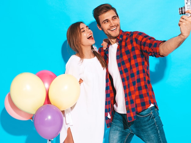 Smiling beautiful girl and her handsome boyfriend holding bunch of colorful balloons. happy couple taking photo of themselves. happy birthday Free Photo
