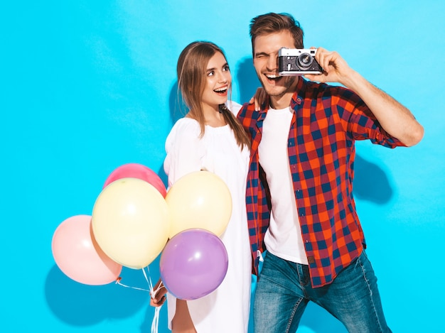 Smiling beautiful girl and her handsome boyfriend holding bunch of colorful balloons. happy couple taking photo of themselves on retro camera. happy birthday Free Photo