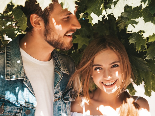 Smiling beautiful girl and her handsome boyfriend posing in the street near tree. Free Photo